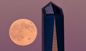 In Spain a plane flies across the supermoon with a Madrid skyscraper in the foreground,