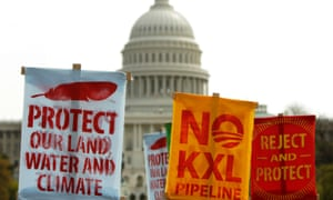Members of the Cowboys and Indian Alliance, a group of ranchers, farmers and indigenous leaders, lift their signs in protest against the Keystone XL pipeline in front of the US Capitol in Washington