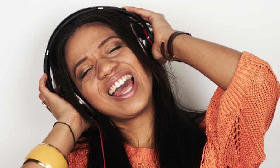 A woman listening to music through headphones