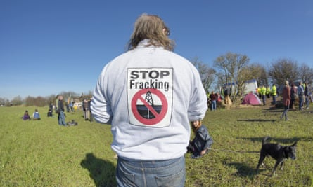 Anti-fracking protestor watching the protest on Barton Moss Road which has been blocked by two protestors using a lock-on device, Manchester, 11 March 2014.