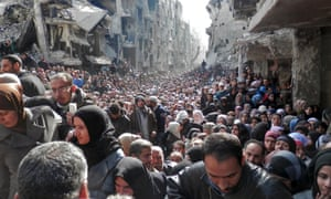 Residents wait in line to receive food aid distributed in the Yarmouk refugee camp on January 31, 2014 in Damascus, Syria. The United Nations renewed calls for the Syria regime and rebels to allow food and medical aid into the Palestinian camp of Yarmouk. An estimated 18,000 people are besieged inside the camp as the conflict in Syria continues.