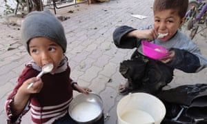 Children eat food distributed to them in the besieged al-Yarmouk camp, south of Damascus April 7, 2014.