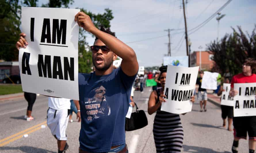 Aaron Coleman, left, joins other protesters marching on Florissant Road in historic downtown Ferguson.