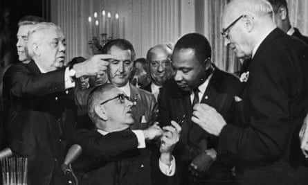 US President Lyndon B Johnson shakes the hand of Dr. Martin Luther King Jr at the signing of the Civil Rights Act while officials look on, Washington DC.
