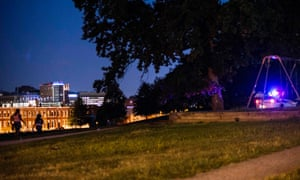 Residents walk through Collington Square Park minutes before a curfew law took effect in Baltimore.