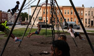 Children play on swings at Collington Square Park an hour before a curfew law took effect in Baltimore.