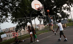 Children play basketball at Collington Square Park less than an hour before a curfew law took effect in Baltimore.