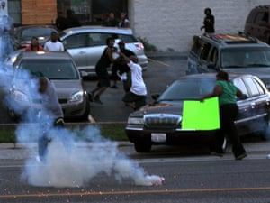 People scatter as police officers fire teargas in Ferguson, Missouri.
