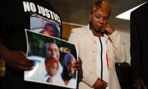 Lesley McSpadden, the mother of 18-year-old Michael Brown, wipes away tears as Brown's father, Michael Brown Sr, holds up a family picture of himself, his son, top left, and a young child.