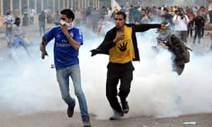 Mohamed Morsi supporters run away from teargas in Rabaa al-Adawiya square