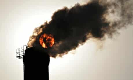 sun seen behind smoke billowing from a chimney of a heating plant in Taiyuan