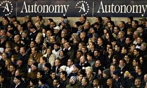 Tottenham Hotspur fans watch their team, beneath an Autonomy advertising hoarding