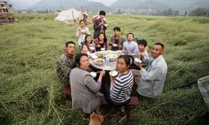 A family meal outside their damaged home after an earthquake in southwest China's Sichuan provinc