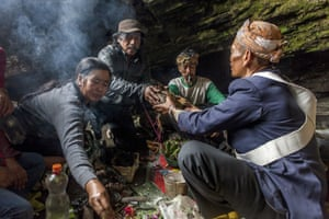 Tenggerese worshippers offer a chicken to a shaman