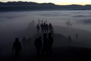 Indonesian villagers walk to the crater during the ceremony at Mount Bromo