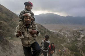 A worshipper carries his son as he climbs the mountain to collect holy water