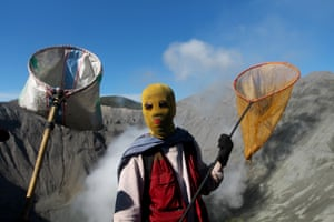 Villagers wait to catch offerings thrown by Hindu worshipers at the crater of Mount Bromo
