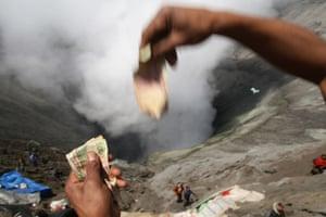 A Tengger tribesman throws money towards the Mount Bromo crater