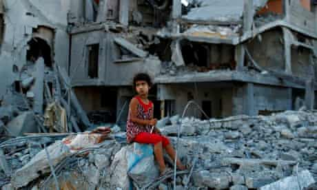 A girl sits on the ruins of her family's home in Gaza