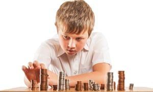 A young boy counts piles of coins