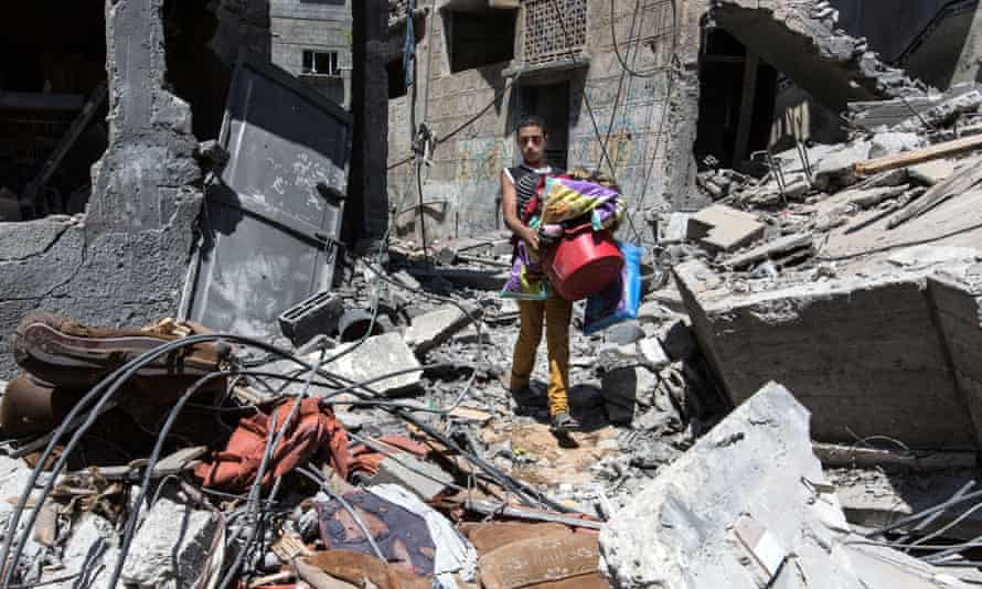 A Gaza resident returns to pick up belongings after his home was turned to rubble. Photograph: Sean Smith