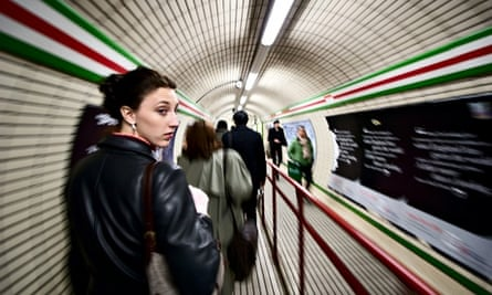 A woman looks back while walking down a hallway connecting two tube stops in the London Underground