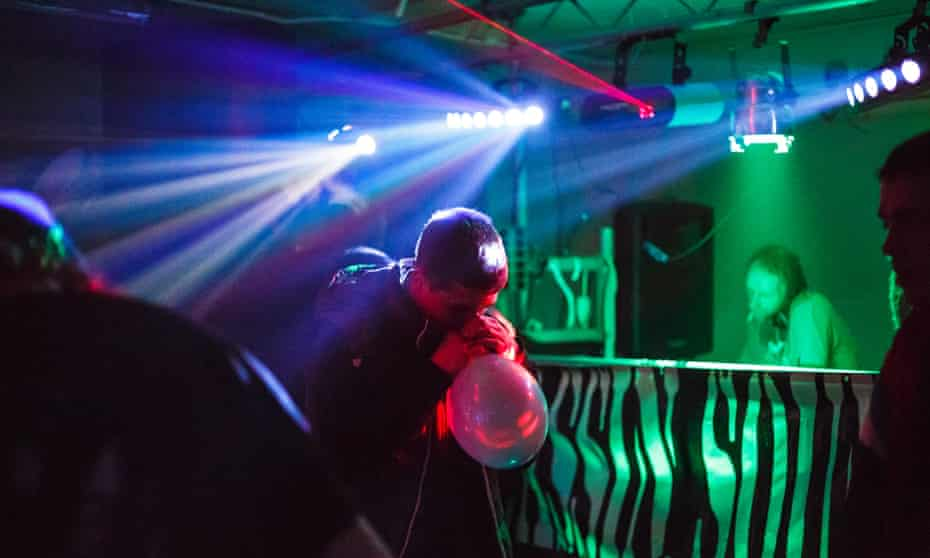 A man inhales nitrous oxide from a balloon at a warehouse rave in east London.