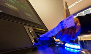 Man putting twenty pound note in fixed odds gaming machine in Corals betting shop. UK