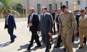Iraqi Prime Minister Nuri al-Maliki  (3rd L) walks in the grounds of the Defence Ministry in the capital Baghdad during the funeral of Major General Majid Abdul Salam, the pilot of a helicopter that crashed the day before  in northern Iraq, on August 13, 2014.