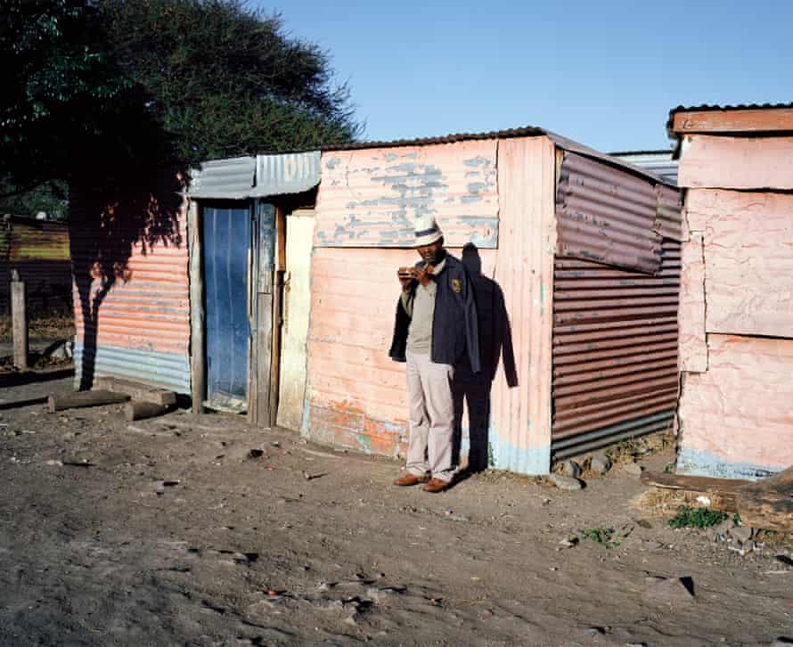 A striking miner waits in the early morning for Mazula's shebeen to open so that he can purchase some home-brewed beer.