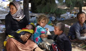 A woman and children fleeing the violence in the Iraqi town of Sinjar wait at the Syrian border.