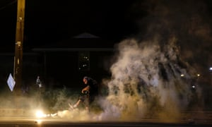 A protester kicks a smoke grenade deployed by police back in the direction of police.