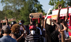Demonstrators raise their hands while protesting against the killing of teenager Michael Brown