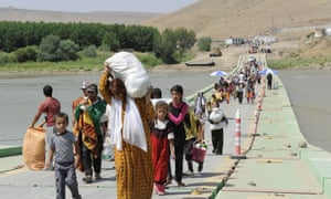 Displaced members of the Yazidi community carrying goods and food cross the Tigris river on the Fayshkhabur bridge.