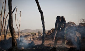 A man looks through the remains of a house destroyed by a Sudan Armed Forces airstrike, in Tabanya, in South Kordofan, a region of Sudan, in 2012.