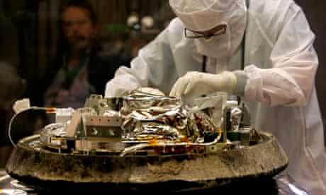 A technician unbolts a canister containing cometary and interstellar dust