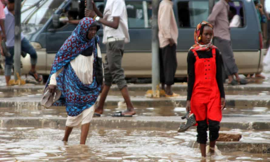 Sudanese people cross flooded streets in Khartoum, on 3 August. According to local media, more than 3000 homes have been destroyed by the deluge.
