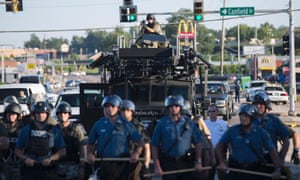 Riot police stand guard before an armoured vehicle and a police armed with a mounted sniper rifle in Ferguson, Missouri.