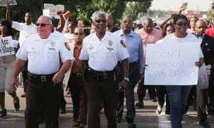 Officers from the Missouri state highway patrol march with demonstrators in Ferguson after taking over from the St Louis county force in policing demonstrations.