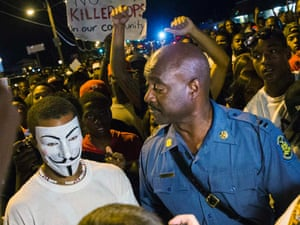 """Missouri State Highway Patrol Captain Ron Johnson speaks to a protester wearing a """"Guy Fawkes"""" mask."""