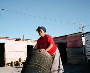 Thembisa's aunt starts preparing the home-brewed beer at the shebeen she runs, Marikana