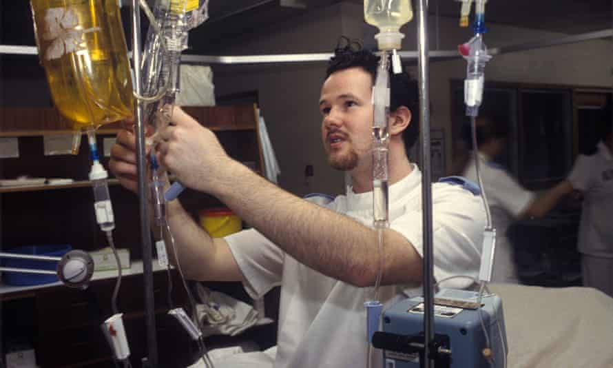 A male nurse checks the drips of a patient in hospital