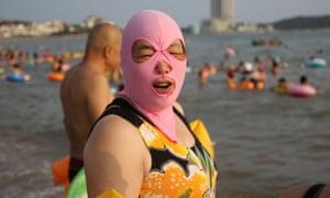 A woman wearing a facekini. Women balaclava style face masks at a beach, Qingdao, Shandong Province, China
