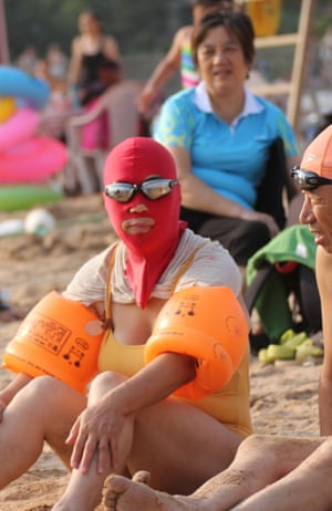 A woman wearing a facekini and armbands rests on the beach.