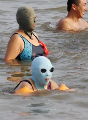 Women wearing facekinis swim.