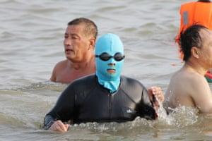A swimmer wearing a facekini walks in the water
