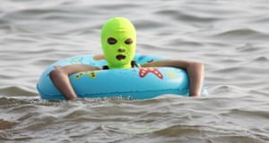 A young girl wearing a facekini swims with a life ring.