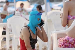 A woman wearing a facekini talks on her phone