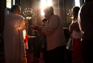 Chinese Catholics take communion during a service for the Assumption of the Virgin Mary in Beijing