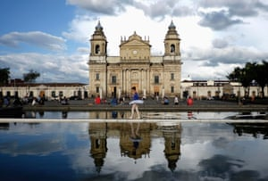 A girl crosses a fountain in front of the cathedral in Guatemala City
